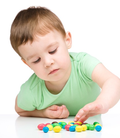 Portrait of a boy with colorful candies, isolated over white photo