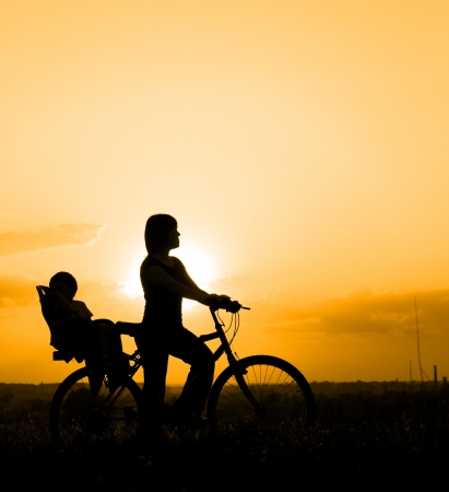 Silhouette of mother riding on a bicycle with her child backlit by sunset Stock Photo - 19915228