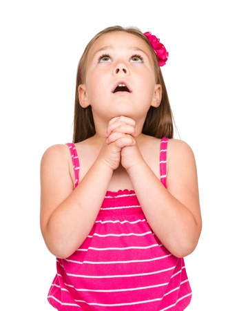 Cute little girl is praying, isolated over white photo