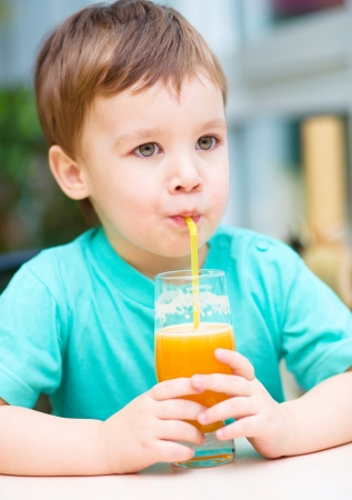 another way: Little boy is drinking orange juice using straw Stock Photo