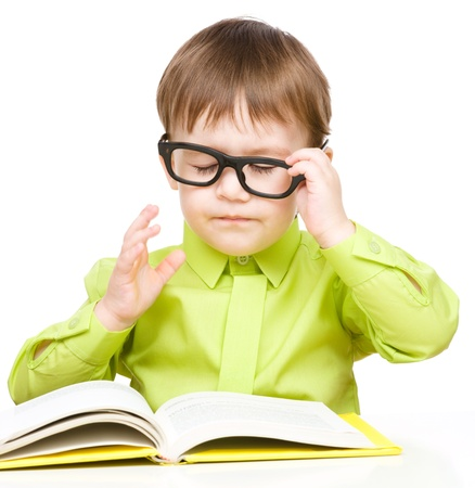 Cute little child play with book and wearing glasses while sitting at table, isolated over white photo