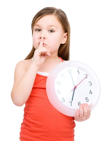seven persons: Little girl is holding big clock and showing hush gesture, isolated over white Stock Photo