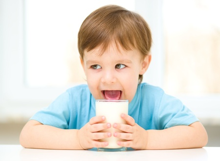 Cute little boy is dipping his tongue in the glass of milk photo