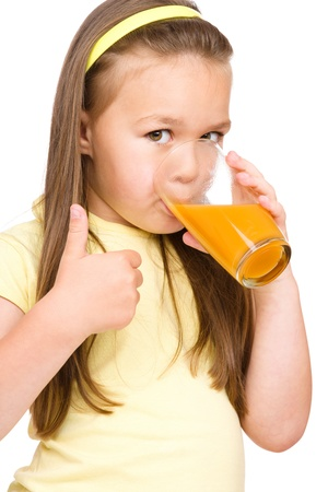 Little girl is drinking orange juice, isolated over white photo