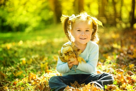 Cute little girl in autumn park holding bunch of yellow leaves Stock Photo - 20674978