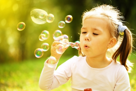 Cute little girl is blowing a soap bubbles photo