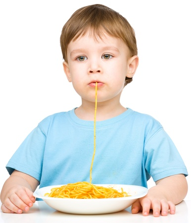 Little boy is sucking up a single spaghetti strand, isolated over white photo