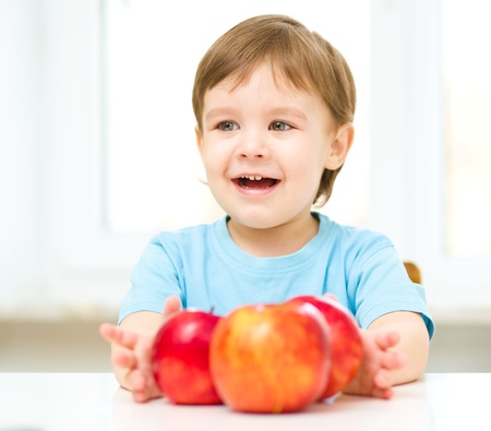 Portrait of a happy little boy with red apples photo