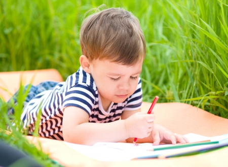 little boy: Little boy is playing with pencils outdoors