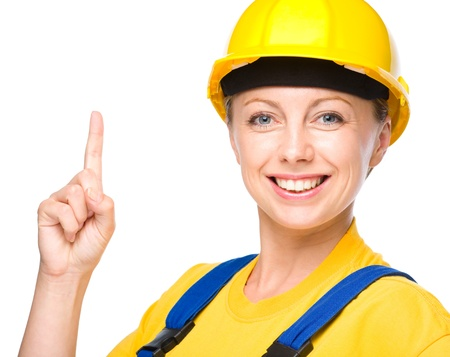 woman pointing up: Young happy lady as a construction worker is pointing up with her forefinger, isolated over white Stock Photo