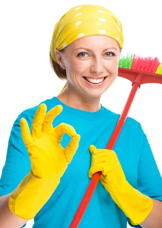all right: Young woman as a cleaning maid holding broom and showing OK sign, isolated over white Stock Photo