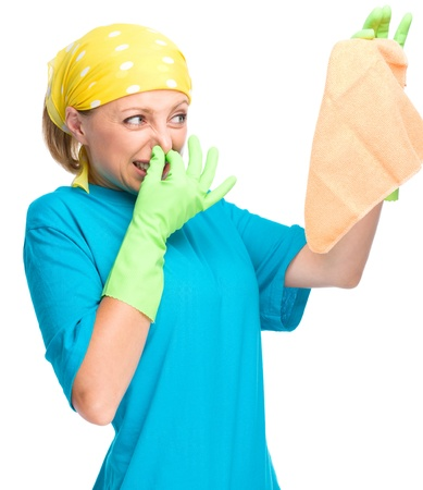 rags: Young woman as a cleaning maid holding rag and pinching her nose because of bad smell, isolated over white Stock Photo