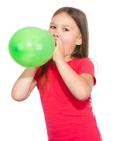 inflating: Little girl is inflating green balloon, isolated over white