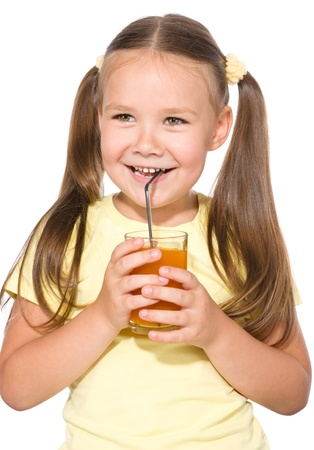 Little girl is drinking carrot juice using straw, isolated over white photo