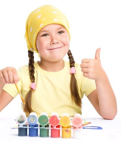 niños jugando en la escuela: Juego de Cute niños alegres con pinturas, mientras que sentado en la mesa y muestra el pulgar hacia arriba gesto, aislado más de blanco Foto de archivo