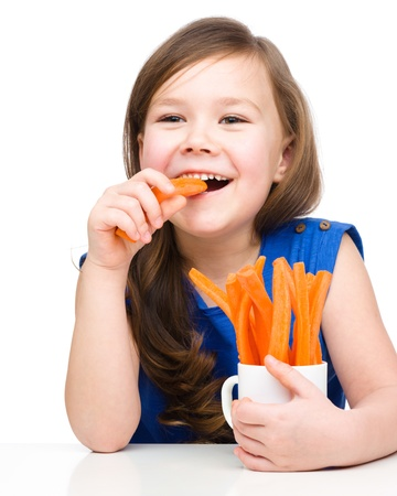snack: Cute little girl is eating carrot, isolated over white Stock Photo
