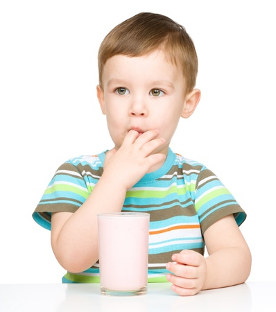 finger licking: Cute little boy with a glass of milk licking his finger, isolated over white