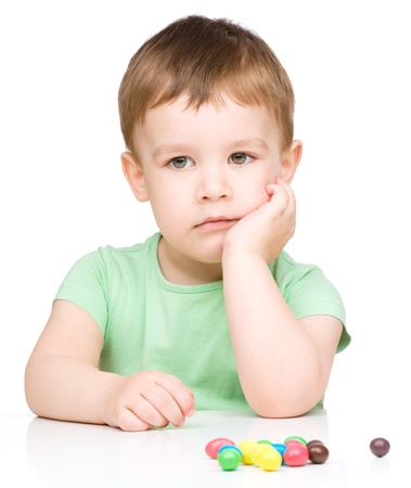 sad boy: Portrait of a sad little boy with colorful candies, isolated over white