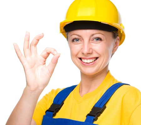 Young happy lady as a construction worker is showing OK sign, isolated over white Stock Photo - 21386153