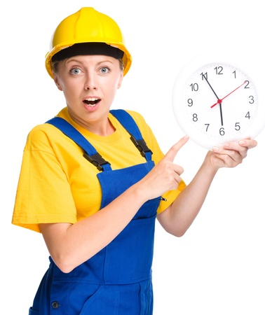 impatient: Young construction worker is pointing at clock showing almost six, isolated over white