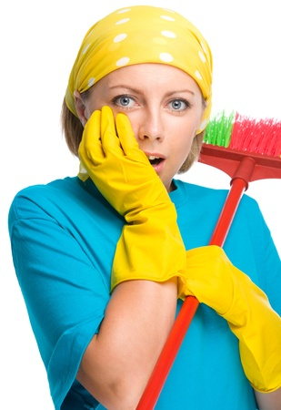 dismay: Young woman - cleaning maid with broom holding her face in astonishment, isolated over white