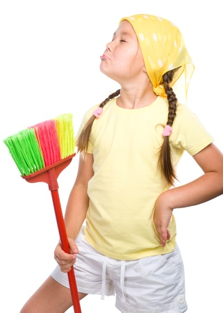 Young girl is posing as a cleaning maid and holding broom, isolated over white photo