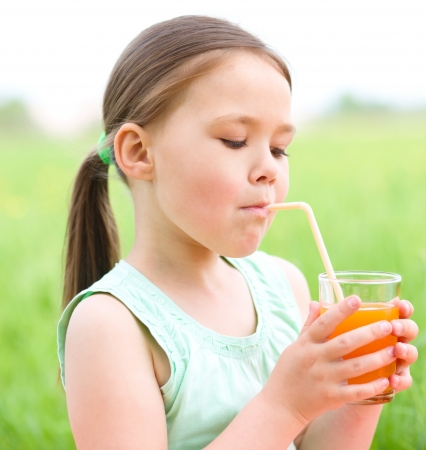 Little girl is drinking orange juice using straw while sitting on green grass photo