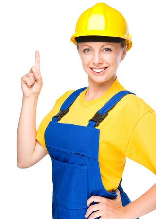 Young happy lady as a construction worker is pointing up with her forefinger, isolated over white photo