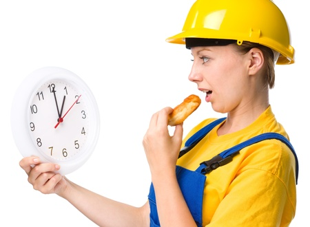 lunchtime: Young happy lady as a construction worker is biting donut while holding big clock, lunchtime concept, isolated over white Stock Photo