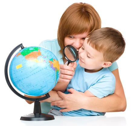 Mother is looking at globe with her son using magnifier, isolated over white photo