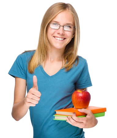 Young skinny student girl is holding exercise books and apple while showing thumb up gesture, isolated over white photo