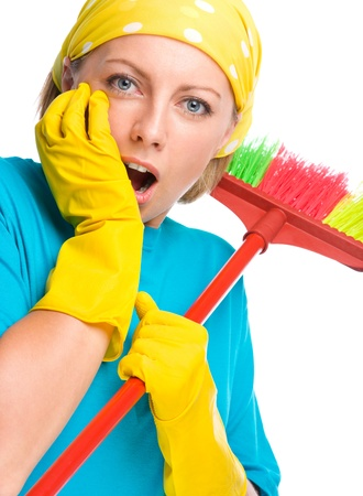 Young woman - cleaning maid with broom holding her face in astonishment, isolated over white photo