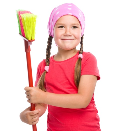 Young girl is dressed as a cleaning maid and holding broom, isolated over white Stock Photo - 21621872