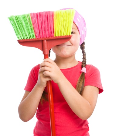 household chores: Young girl is dressed as a cleaning maid and hiding behind broom, isolated over white