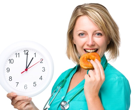 lunchtime: Young happy lady wearing doctor uniform is biting donut while holding big clock, lunchtime concept, isolated over white