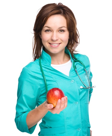Young lady doctor is holding a red apple, isolated over white photo