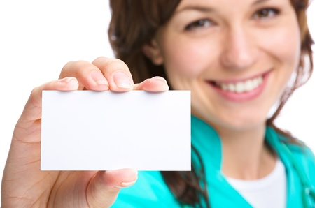 holding close: Young woman doctor is showing her business card, isolated over white Stock Photo