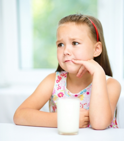 disobey: Sad little girl refuses to drink a glass of milk Stock Photo