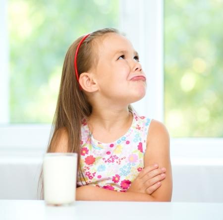 petite fille triste: Petite fille triste refuse de boire un verre de lait
