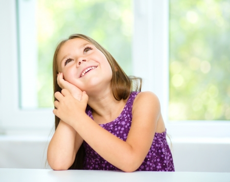 guessing: Little girl is daydreaming while sitting at table, isolated over white Stock Photo