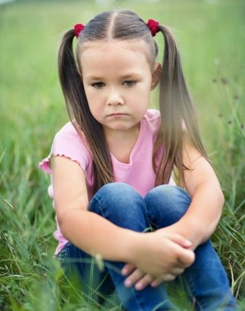 petite fille triste: Petite fille triste est assis sur l'herbe verte, pousse ext�rieure