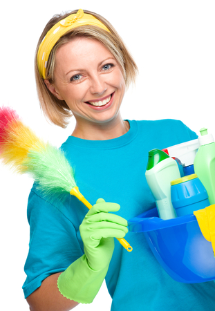 housewife gloves: Young woman as a cleaning maid holding bucket full of liquids and static duster, isolated over white Stock Photo