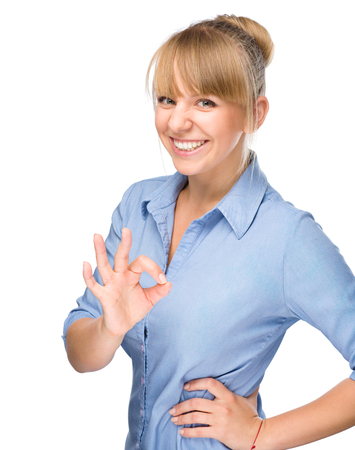 Young woman is showing OK sign, isolated over white photo