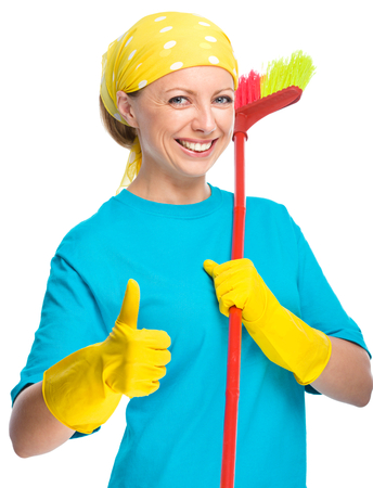Young woman as a cleaning maid holding broom and showing thumb up gesture, isolated over white Stock Photo - 22448765