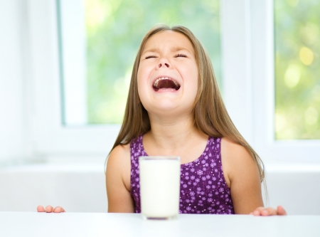 Sad little girl refuses to drink a glass of milk Imagens
