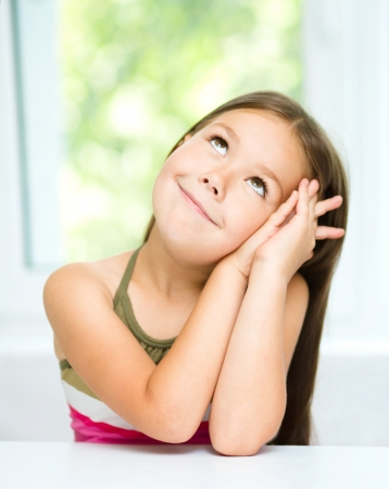 Little girl is daydreaming while sitting at table photo