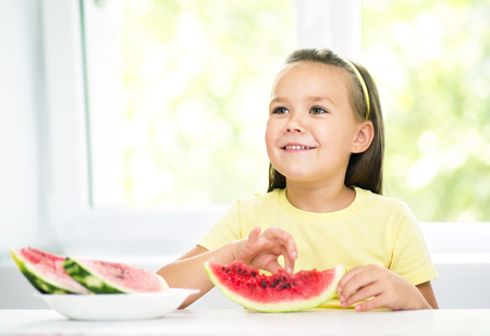 Cute little girl is eating watermelon, isolated over white photo