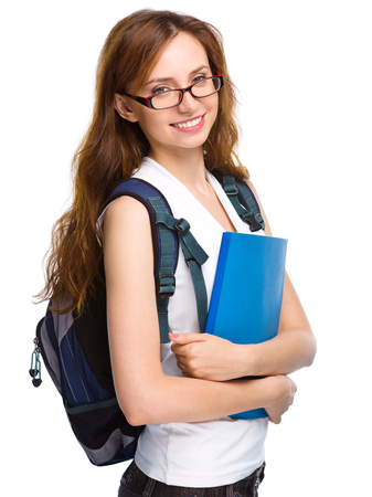 Young student girl is holding exercise book, isolated over white photo