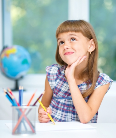 and guessing: Little girl is drawing using color pencils and daydreaming while sitting at table, isolated over white