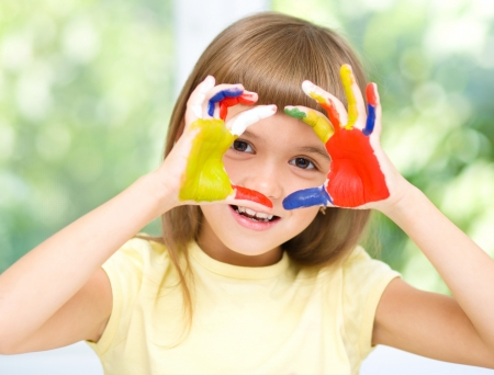 fingerpaint: Portrait of a cute cheerful girl showing her hands painted in bright colors